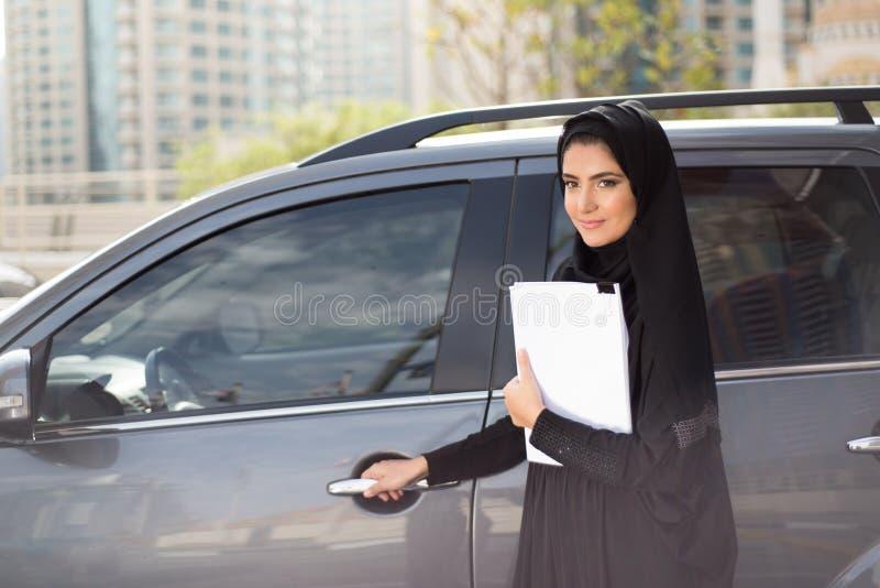 Mulher de negócio árabe que está ao lado de um carro fotos de stock