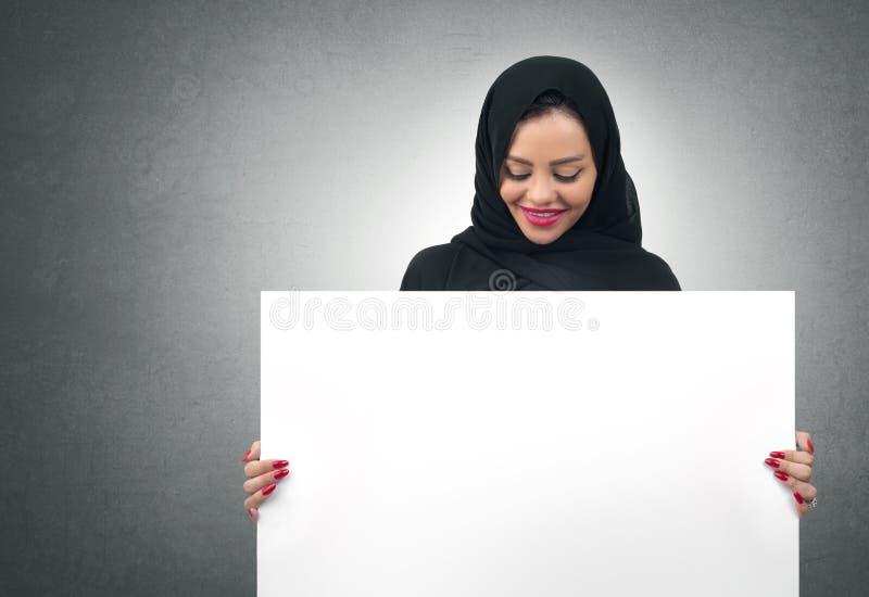 Mulher de negócio árabe que mantém uma placa branca isolada imagens de stock royalty free