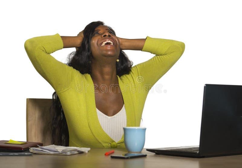 Mulher de negócio afro-americana preta feliz e atrativa nova que sorri trabalho alegre e seguro na celebridade da mesa do computa imagens de stock