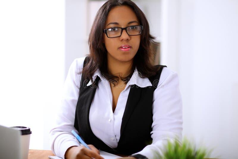 A mulher de negócio afro-americano é ocupada com trabalho de papel no escritório imagem de stock