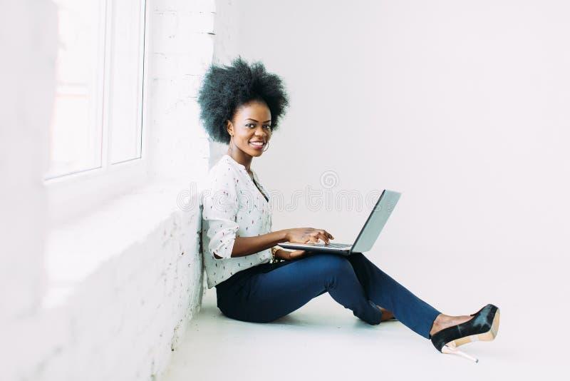 Mulher de negócio afro-americano nova que usa o portátil, ao sentar-se no assoalho perto de uma janela grande no estúdio fotografia de stock