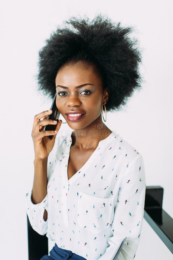 Mulher de negócio afro-americano de sorriso nova que usa o telefone, isolado no branco fotos de stock