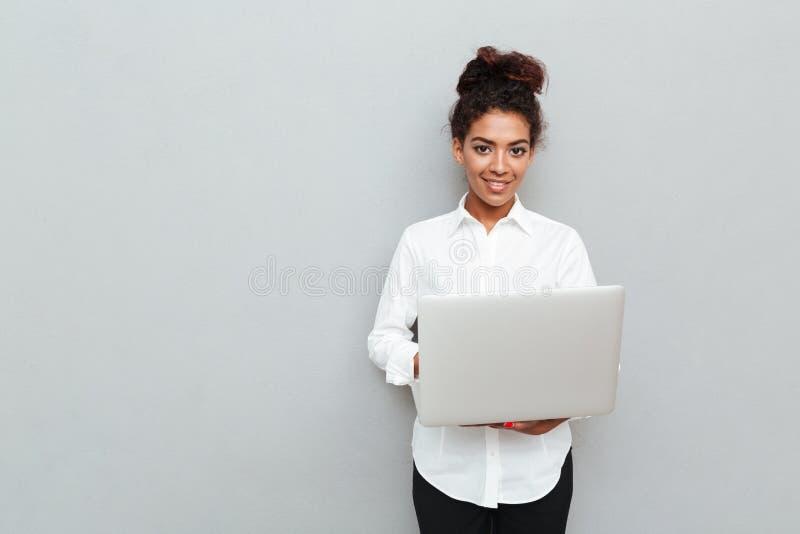Mulher de negócio alegre africana que está sobre a parede cinzenta imagens de stock