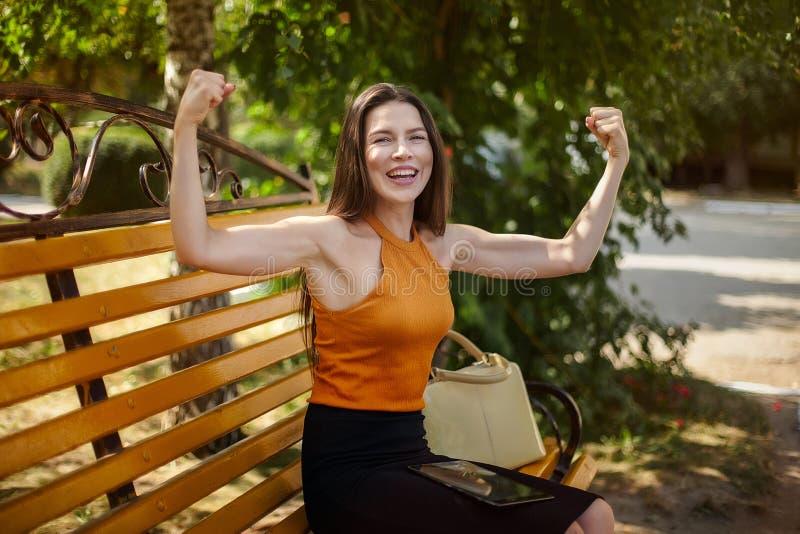 A mulher de negócio alegre e feliz mostra gestos com poder Mãos acima, esporte e negócio imagens de stock