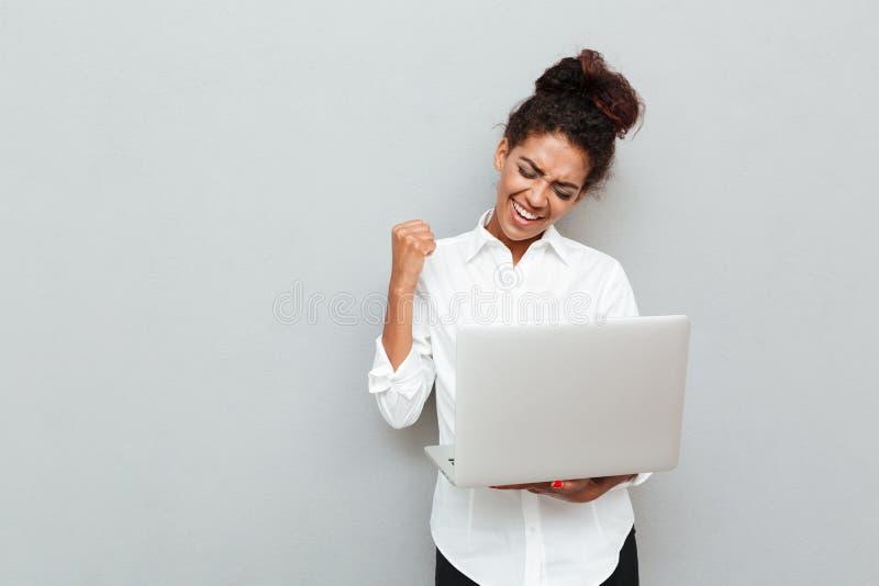 A mulher de negócio alegre faz o gesto do vencedor fotografia de stock royalty free