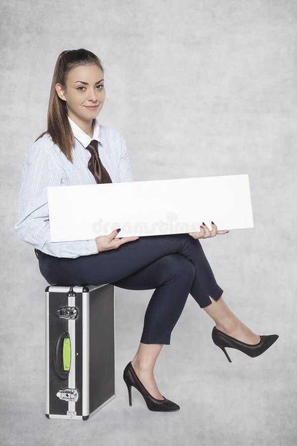 A mulher de negócio alegre senta-se em uma mala de viagem e guarda-se um anúncio publicitário imagens de stock