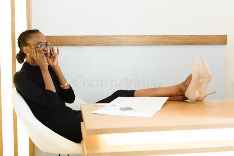 A mulher de negócio americana africana ou preta elegante, vidros vestindo, sentando-se com pés em estiletes bege bombeia sapatas  fotografia de stock royalty free