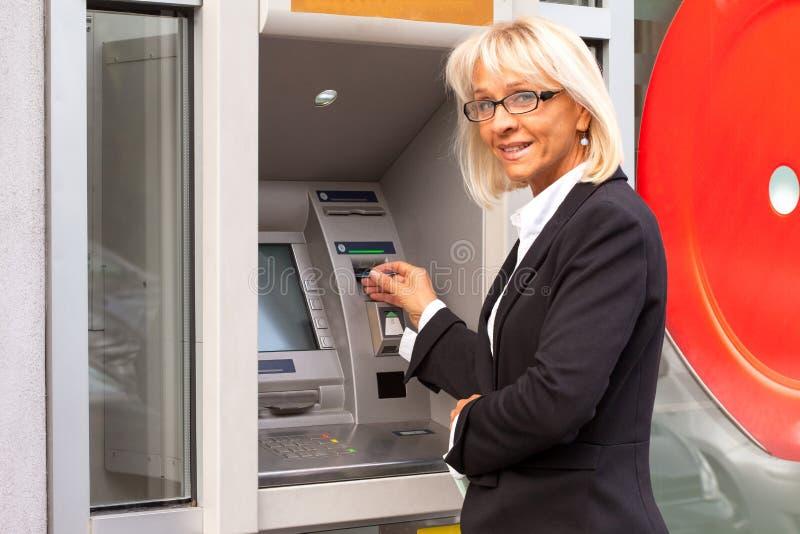 Mulher de negócio ao lado do ATM fotografia de stock