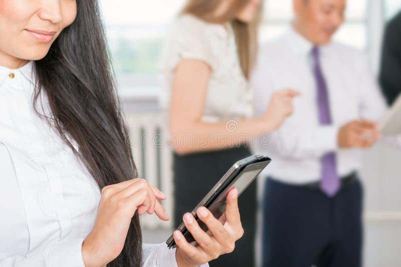 Mulher de negócio asiática bem sucedida da imagem do close up que usa o telefone celular imagens de stock