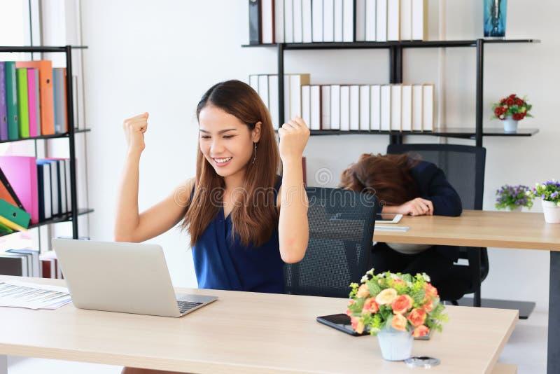 Mulher de negócio asiática bem sucedida que levanta as mãos com curvatura do colega do concorrente abaixo da cabeça na mesa no es imagens de stock