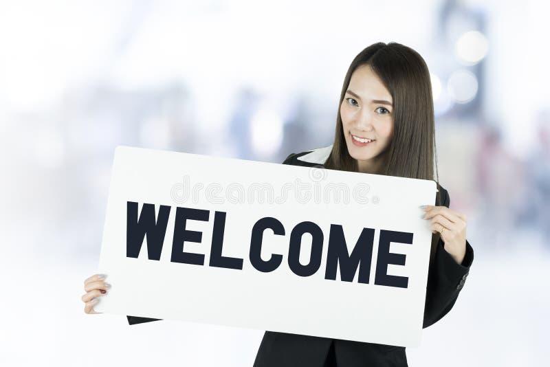Mulher de negócio asiática com o cabelo longo que guarda uma placa do sinal bem-vindo fotografia de stock royalty free