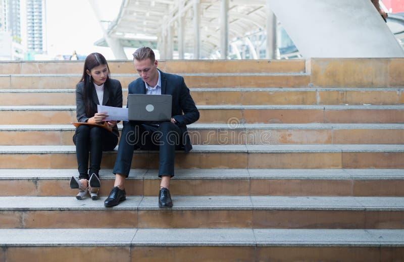 A mulher de negócio asiática e o homem de negócios caucasiano sentam-se na escadaria e guardam-se um papel do relatório financeir imagens de stock royalty free
