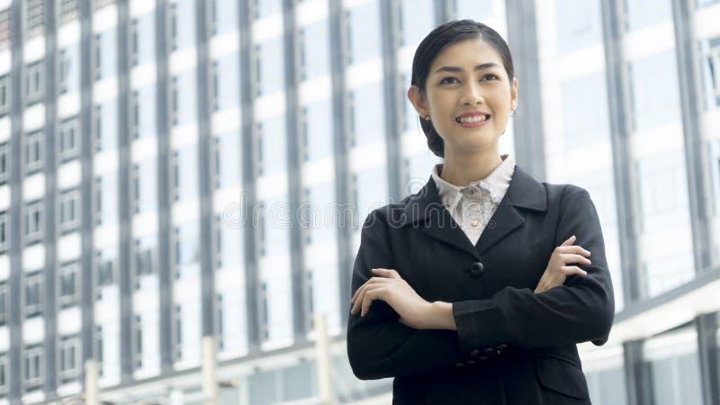 A mulher de negócio asiática está com postagem segura em exterior foto de stock royalty free