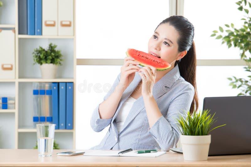 Mulher de negócio asiática feliz a comer a melancia fresca imagens de stock