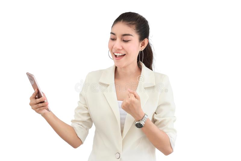A mulher de negócio asiática nova alegre que sorri e que olha o telefone esperto móvel em suas mãos no branco isolou o fundo fotos de stock