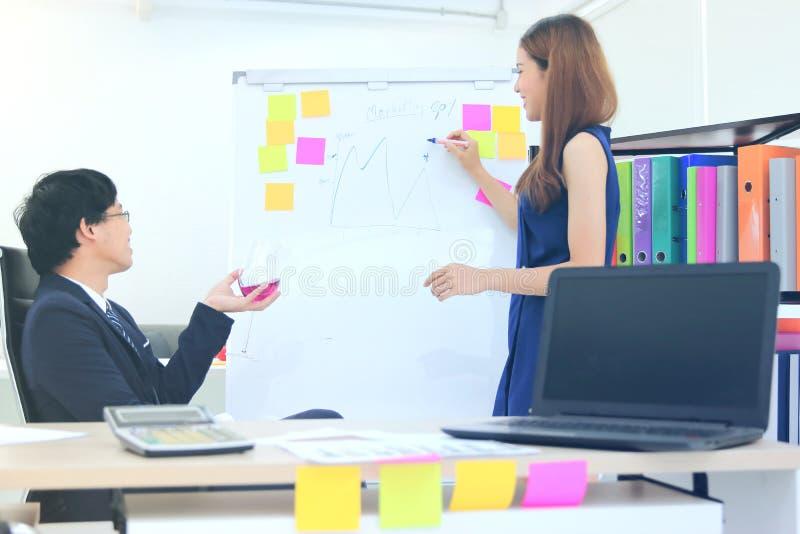 Mulher de negócio asiática nova atrativa que explica estratégias na carta de aleta ao executivo na sala de reuniões imagens de stock