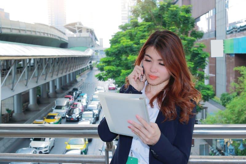 Mulher de negócio asiática nova atrativa que fala no telefone e que examina arquivos de original em suas mãos o fundo exterior do fotos de stock royalty free