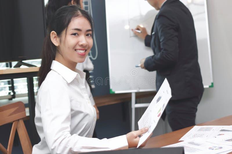 Mulher de negócio asiática nova da liderança que olha a câmera entre a escuta a apresentação no fundo moderno do escritório foto de stock