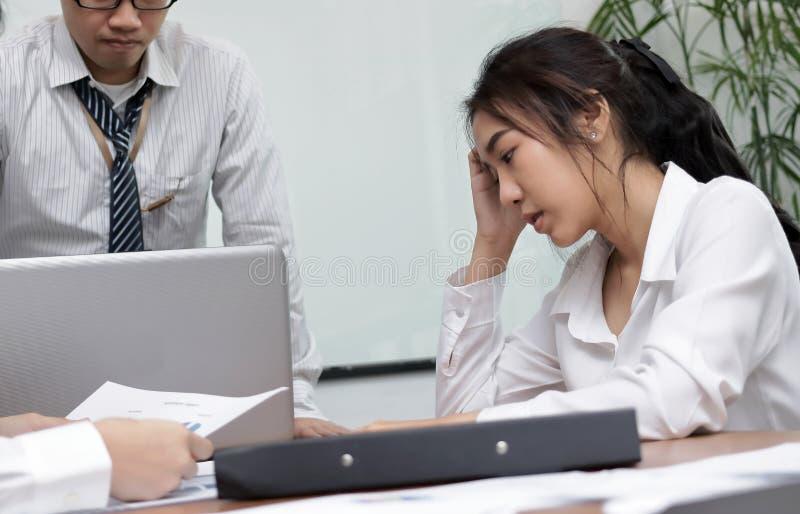 Mulher de negócio asiática nova deprimida frustrante com mãos na cara que sofre do problema severo entre a reunião no escritório imagem de stock royalty free
