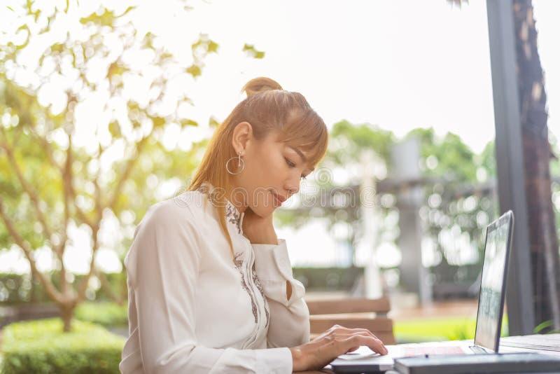 Mulher de negócio asiática nova que trabalha no escritório usando o laptop e a tabuleta digital imagem de stock royalty free