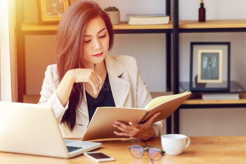 Mulher de negócio asiática nova que trabalha no local de trabalho fotografia de stock
