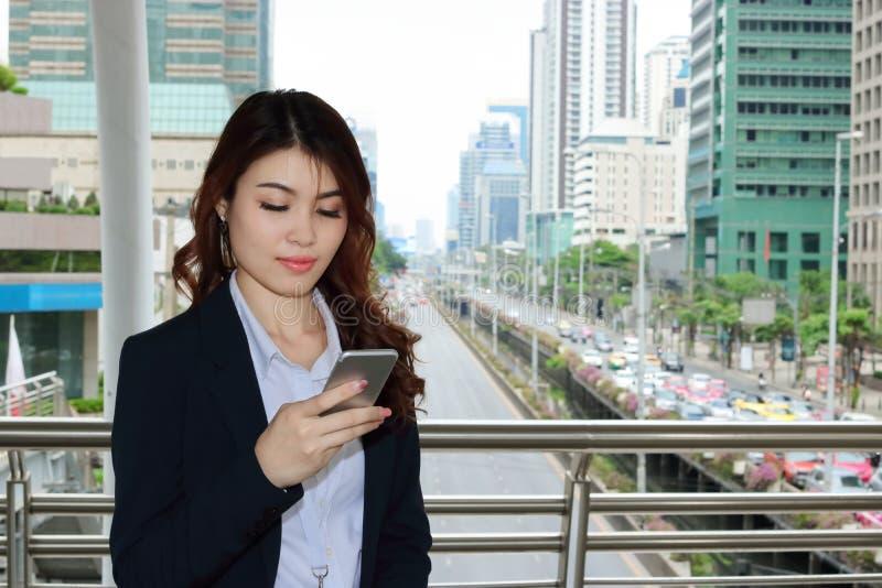 Mulher de negócio asiática nova segura que examina o telefone esperto móvel em suas mãos o fundo urbano da cidade da construção fotografia de stock