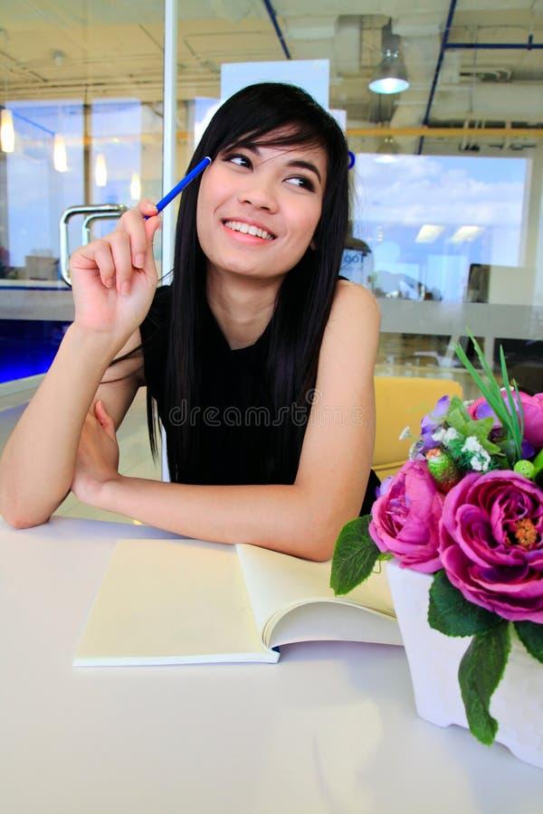 Mulher de negócio asiática que escreve uma nota no escritório foto de stock