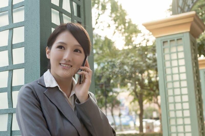 Mulher de negócio asiática que fala no smartphone com copyspace fotos de stock royalty free