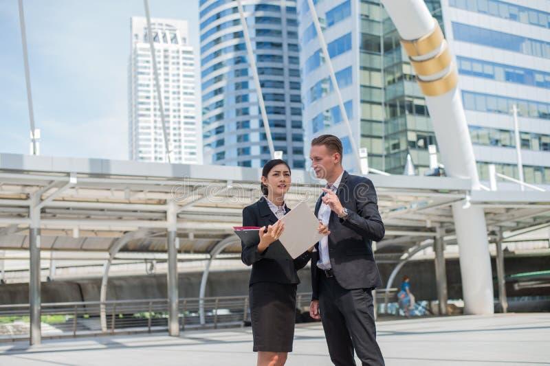 A mulher de negócio asiática que guarda o original e aponta seu dedo a construir e a discutir o futuro do negócio com o homem de  fotos de stock