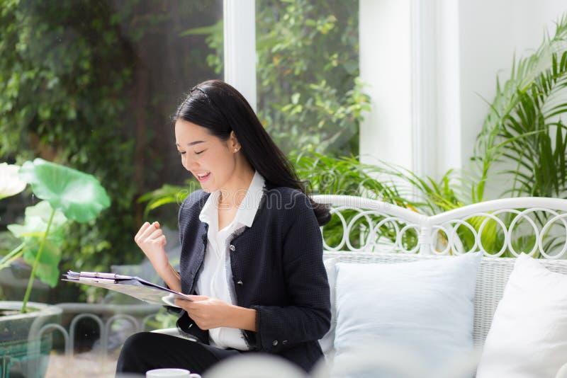 Mulher de negócio asiática que guardam o dobrador da prancheta e gesto contente no escritório foto de stock royalty free
