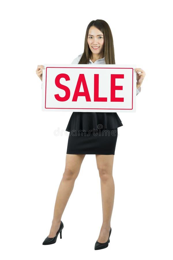 Mulher de negócio asiática que sorri e que guarda o sinal da venda Mulher caucasiano nova bonita foto de stock