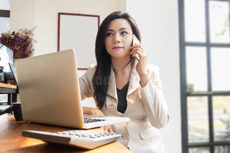 Mulher de negócio asiática que trabalha com caderno do portátil e móbil do uso imagem de stock royalty free