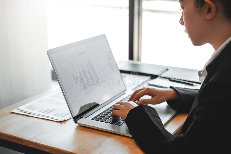 Mulher de negócio asiática que usa o projeto novo do funcionamento do laptop que discute dados financeiros do gráfico do plano no imagem de stock royalty free