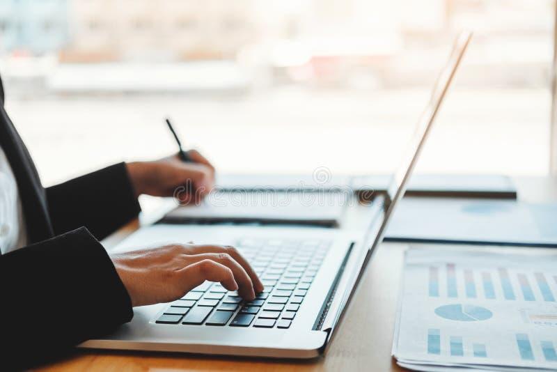Mulher de negócio asiática que usa o projeto novo do funcionamento do laptop que discute dados financeiros do gráfico do plano no imagens de stock royalty free