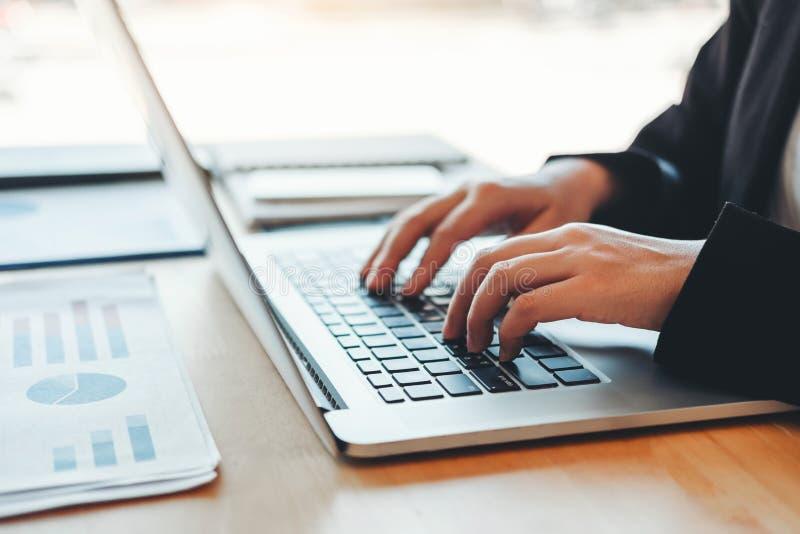 Mulher de negócio asiática que usa o projeto novo do funcionamento do laptop que discute dados financeiros do gráfico do plano no foto de stock