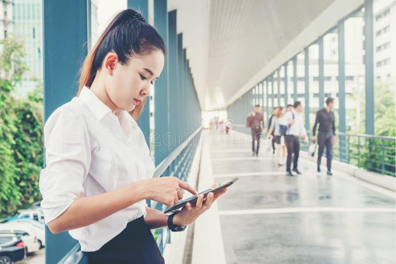 Mulher de negócio asiática que usa o smartphone para o trabalho foto de stock