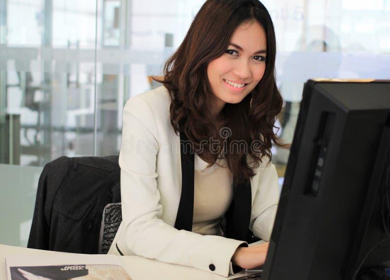 Mulher de negócio asiática que usa um computador imagens de stock royalty free