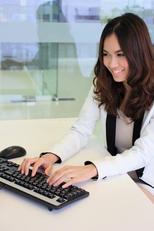 Mulher de negócio asiática que usa um computador fotos de stock royalty free