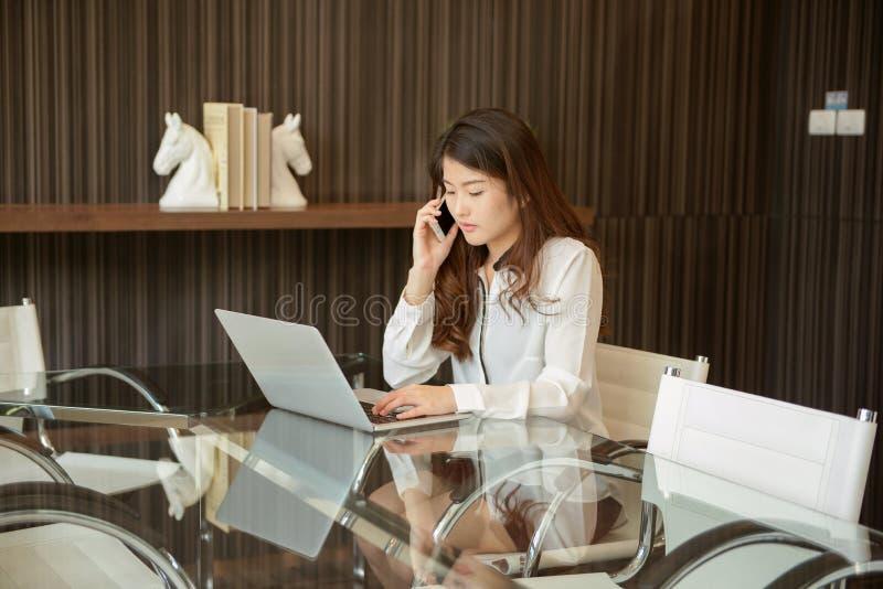 Mulher de negócio asiática que usa um telefone na frente de um portátil fotos de stock royalty free