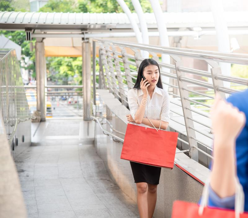 Mulher de negócio asiática segura nova que fala no telefone celular com os sacos de compras coloridos que andam no shopping na  imagem de stock royalty free