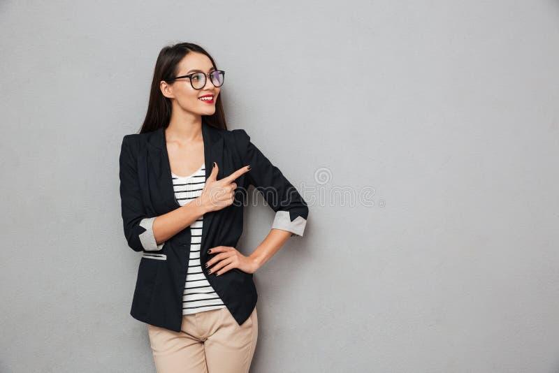 Mulher de negócio asiática de sorriso nos monóculos com o braço no quadril fotografia de stock royalty free