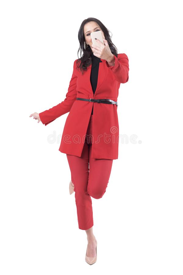 Mulher de negócio atrativa brincalhão no terno que toma o selfie que equilibra em um pé imagens de stock royalty free