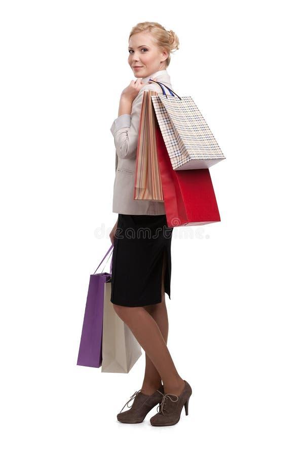 Mulher de negócio atrativa loura em um terno bege claro que guardara sacos de compras imagem de stock