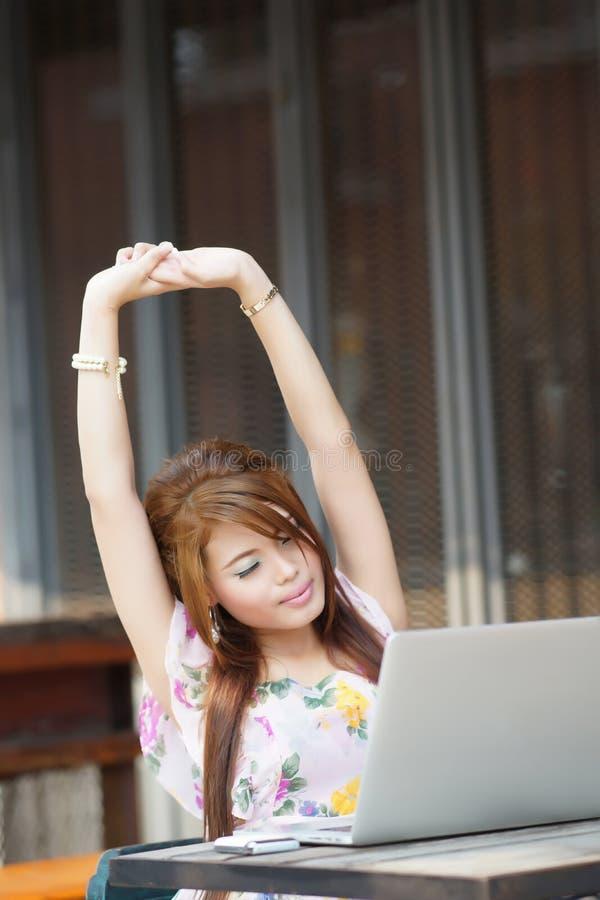Mulher de negócio atrativa nova cansado e que estica em seu lapt fotografia de stock royalty free