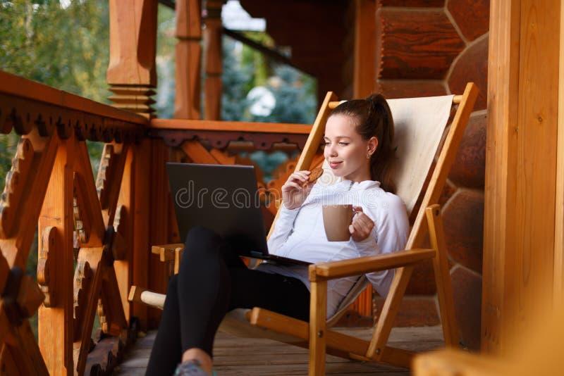 A mulher de negócio atrativa nova está trabalhando no portátil no resort de montanha com um copo do chá e da cookie A fêmea relax fotografia de stock