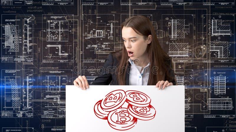 Mulher de negócio de Bauty que está no terno com logotipo de Bitcoin para ilustrar o uso do bitcoin para a troca ou a transferênc fotos de stock royalty free