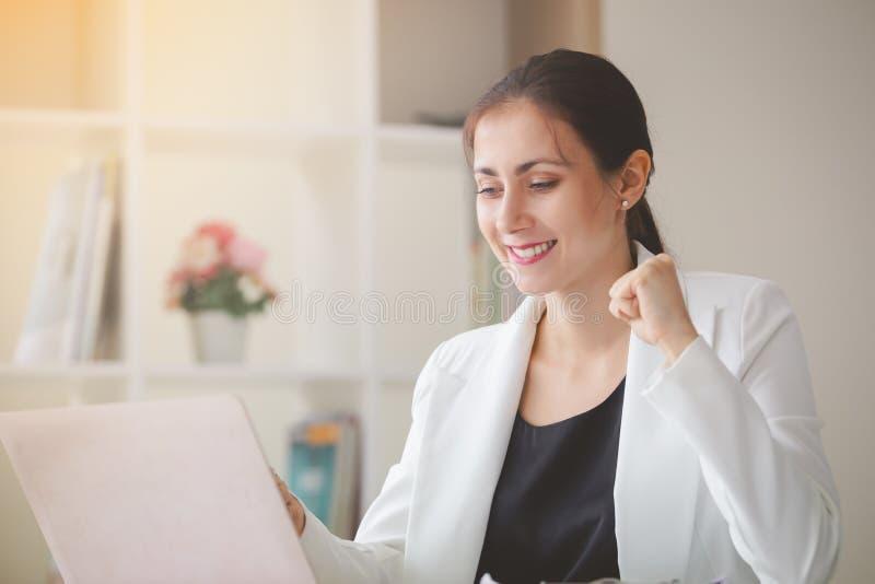 Mulher de negócio bem sucedida que olha o portátil com braços acima fotos de stock royalty free