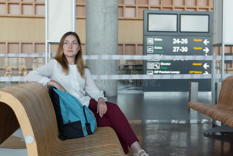 A mulher de negócio bonita com trouxa senta-se ao esperar seu voo imagens de stock