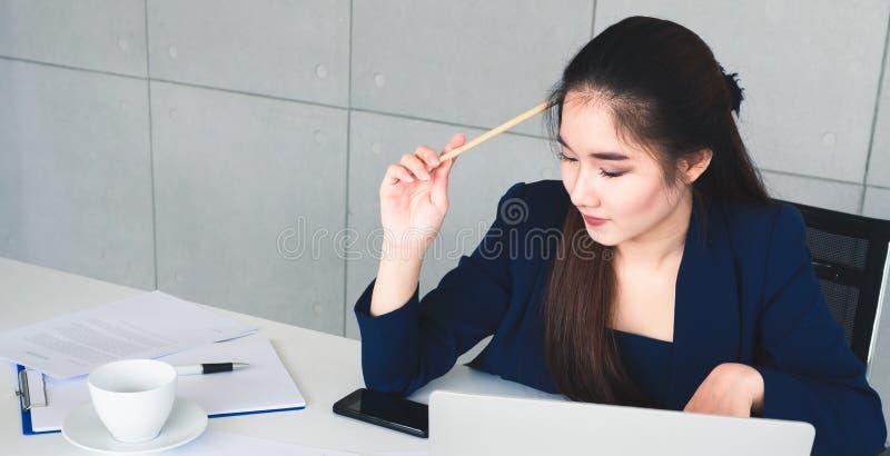 Mulher de negócio bonita do cabelo longo asiático no terno dos azuis marinhos que pensa sobre a solução de seu trabalho Senta-se  fotos de stock royalty free