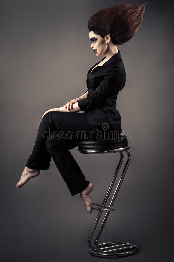 Mulher de negócio bonita elegante que senta-se no tamborete de barra com cabelo luxúria e composição escura foto de stock royalty free